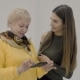 Young and Old Women Discuss Made Photos Looking at Screen of Smartphone - VideoHive Item for Sale