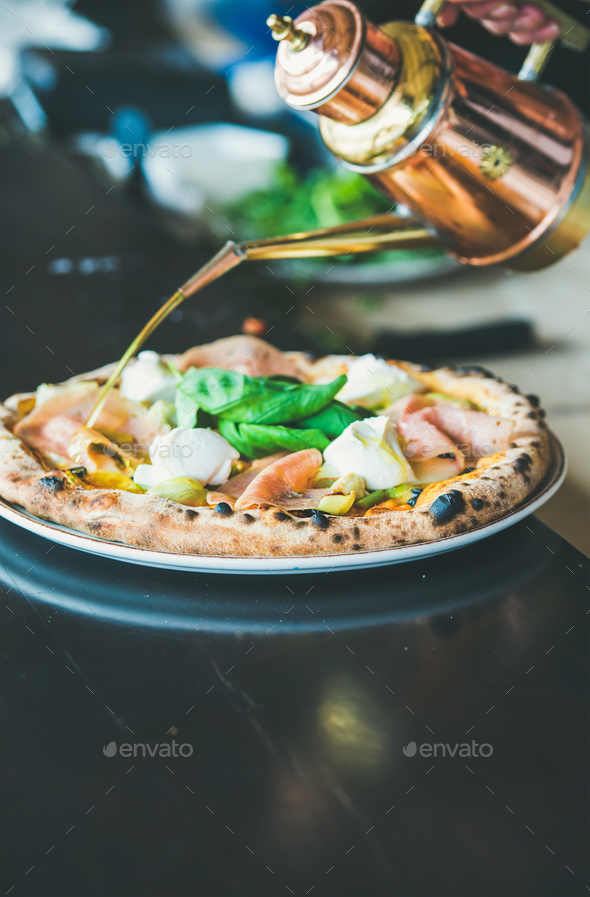 Freshly baked Italian pizza with ham, artichokes served in restaurant - Stock Photo - Images