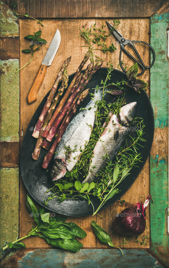 Raw incooked sea bass with herbs - Stock Photo - Images