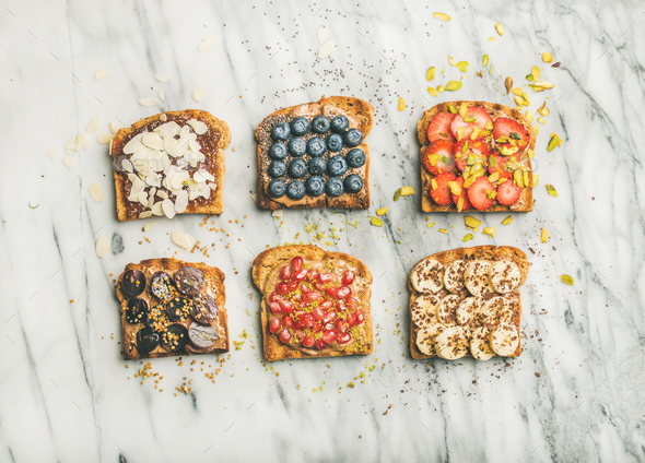 Vegan whole grain toasts with fruit, seeds, nuts, peanut butter - Stock Photo - Images