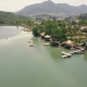 Aerial View Summer Houses with Thatched Roof and Boat Pier on Shore in Mountain Lake Among Tropical - VideoHive Item for Sale