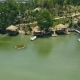 Wooden Bungalows with Thatched Roof and Boat Pier on Shore Green Lake in Resort Hotel Drone View - VideoHive Item for Sale