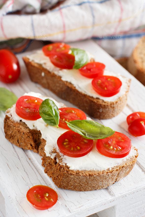 Bruschetta with cream cheese, cherry tomatoes and basil - Stock Photo - Images