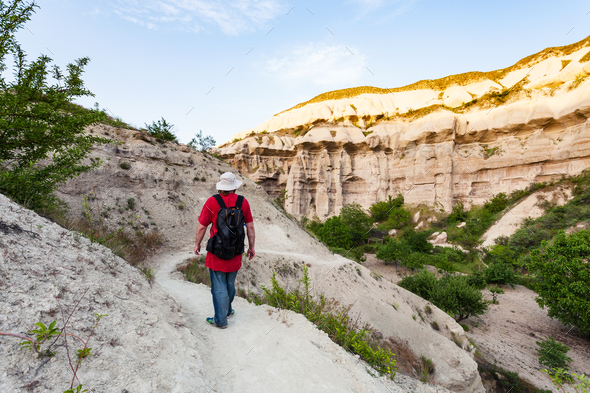ourist on rock slope in gorge near Goreme town - Stock Photo - Images