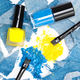 Blue and yellow eyeshadow with nail polishes of the same colors - PhotoDune Item for Sale