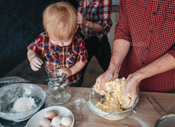 Little son helps in the kitchen to dad and mom - Stock Photo - Images