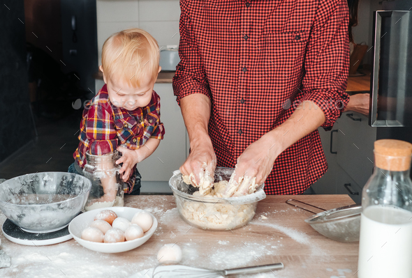 Dad and son make dough in the kitchen - Stock Photo - Images