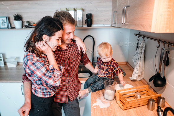 Dad, mom and little son cook a pie - Stock Photo - Images