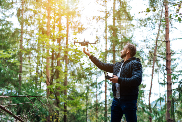 guy starts a quadrocopter in the forest - Stock Photo - Images