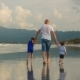 Young Family, a Father with His Son and Daughter, Walks Along the Shore of the Ocean, on the Coast - VideoHive Item for Sale