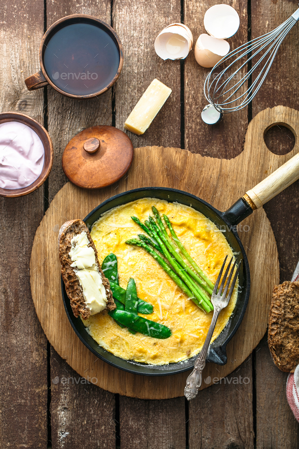 Omelet with green asparagus, pea on frying pan, top view, rustic style - Stock Photo - Images