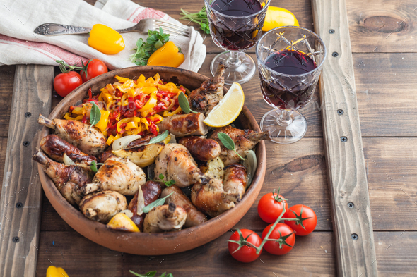 Roasted chicken with sausages and lemon. Tomatoes and wine - Stock Photo - Images