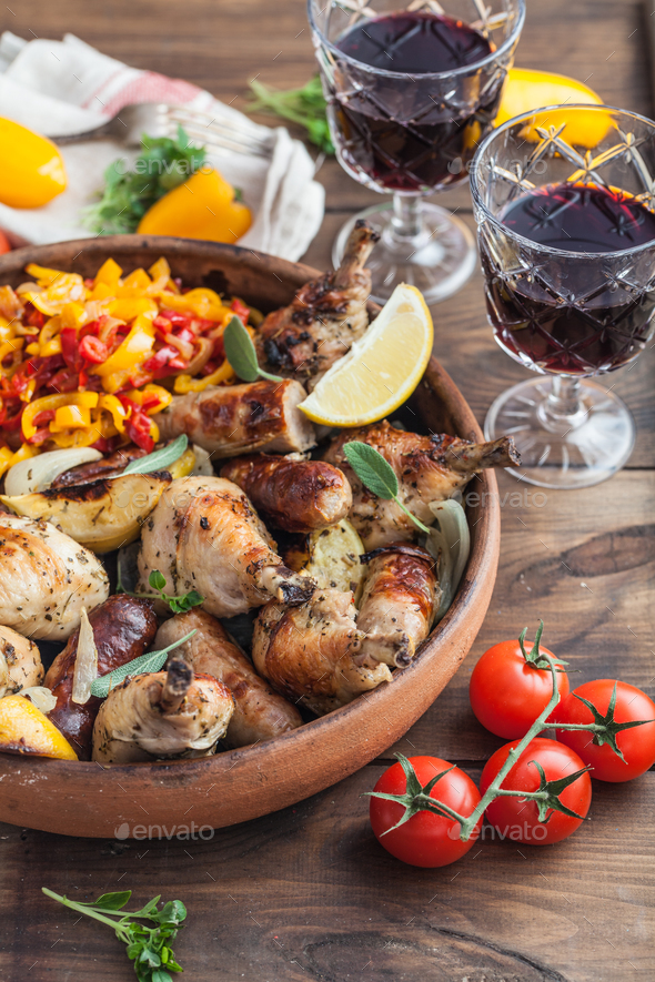Chicken legs roasted with sausages and vegetables. - Stock Photo - Images