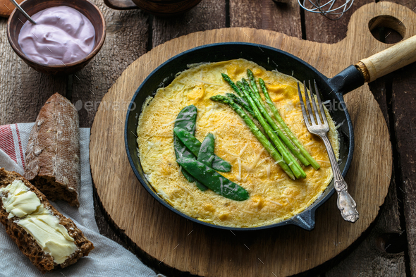 Frittata with green asparagus, pea on frying pan, top view, rustic style - Stock Photo - Images