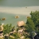 Tropical Bungalows with Thatched Roof and Boat Pier on Shore Green Lake in Resort Hotel Mountain - VideoHive Item for Sale