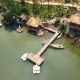 Bungalows with Thatched Roof and Boat Pier on Shore Green Lake Aerial View. Summer Houses on Shore - VideoHive Item for Sale