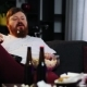 Smiling Fat Man with Beard Watches TV in the Room and Eats Pop-corn at the Table with Beer. Fat Man - VideoHive Item for Sale