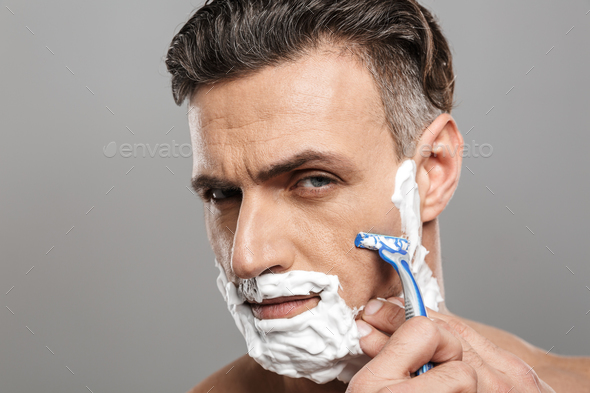 Handsome mature concentrated man naked shaving. - Stock Photo - Images