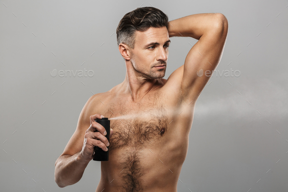 Mature man standing holding deodorant. - Stock Photo - Images