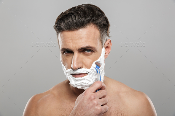 Mature man shaving with razor. - Stock Photo - Images