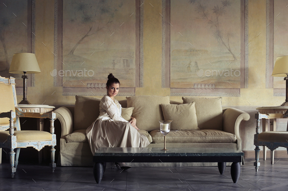Girl sitting on a sofa - Stock Photo - Images
