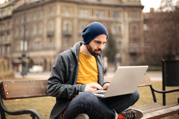 Man using a laptop outdoor - Stock Photo - Images