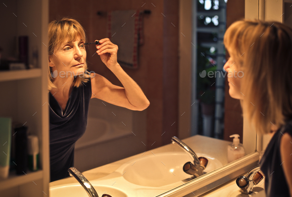 Woman applying make up - Stock Photo - Images