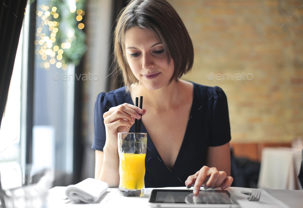Girl in a bar with a tablet - Stock Photo - Images