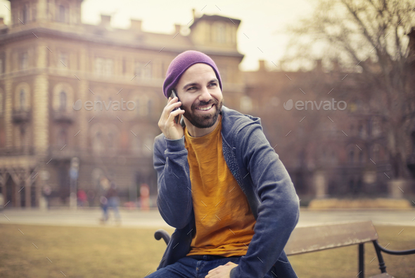 Man taking at the phone outdoor - Stock Photo - Images