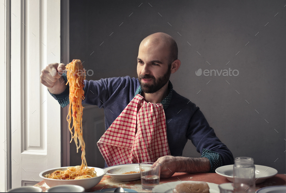 Man eating pasta - Stock Photo - Images