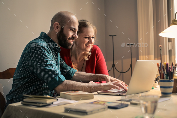 A man and a woman in front of a laptop - Stock Photo - Images