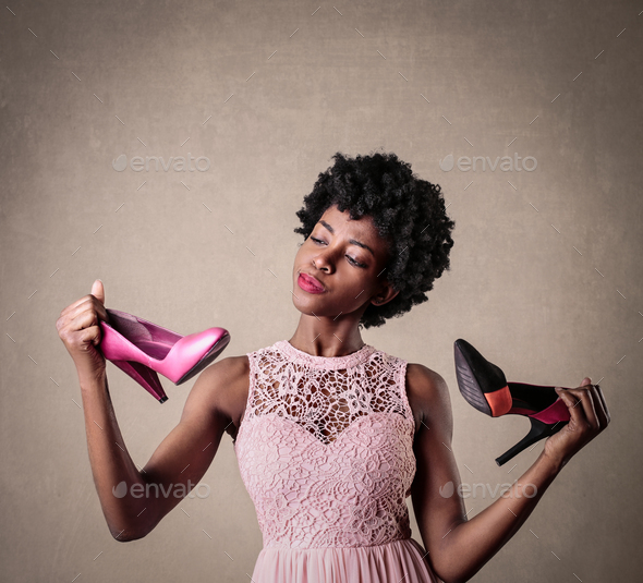 Girl choosing between two pairs of shoes - Stock Photo - Images