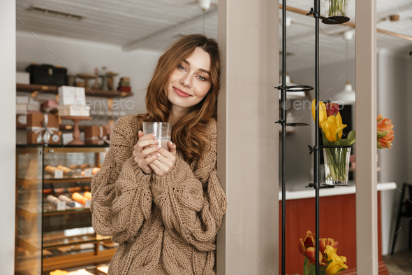 Photo of relaxed woman 20s looking on camera, and drinking glass - Stock Photo - Images