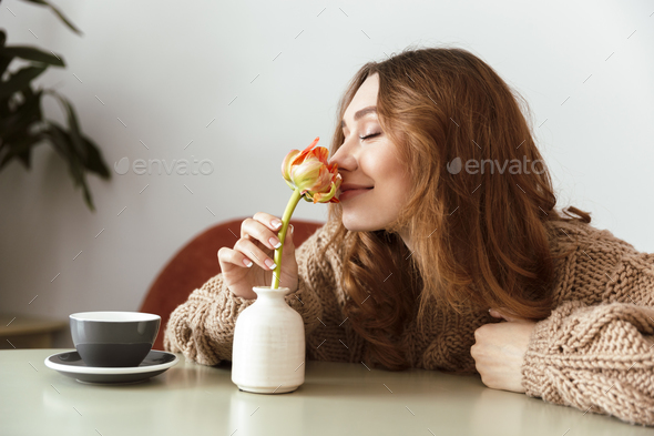 Photo of lovely woman sitting at table in cafe and smelling flow - Stock Photo - Images