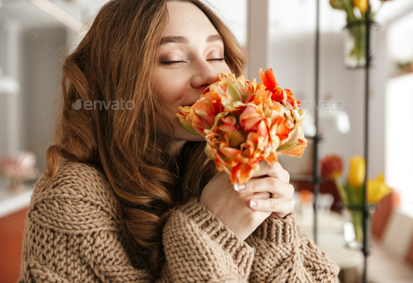 Photo of tender woman in sweater smelling beautiful flower with - Stock Photo - Images