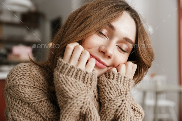 Portrait closeup of attractive woman in knitted sweater, sitting - Stock Photo - Images