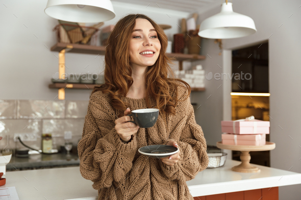 Pleased brunette woman looking aside and smiling, while drinking - Stock Photo - Images