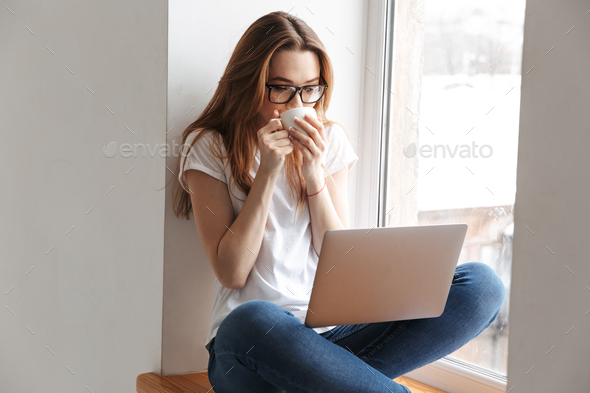 Pretty woman in t-shirt and eyeglasses sitting on windowsill - Stock Photo - Images