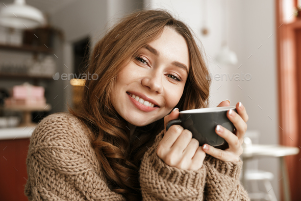 Portrait closeup of satisfied woman in knitted sweater, sitting - Stock Photo - Images