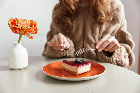 Close up of a woman in sweater eating cheesecake - Stock Photo - Images