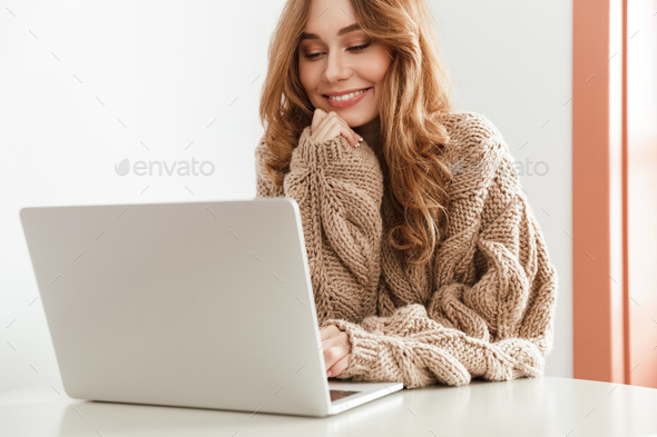 Beautiful woman 20s in sweater with long brown hair using notebo - Stock Photo - Images