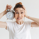 Worried woman in casual clothes holding alarm clock - PhotoDune Item for Sale