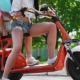 Sexy Girls with Sweet Cotton in Short Shorts Ride an Electric Scooter in the Park - VideoHive Item for Sale