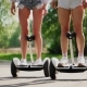 Camera Rises From Bottom To Top Girl in Shorts Stands on White Self-balancing Scooter - VideoHive Item for Sale