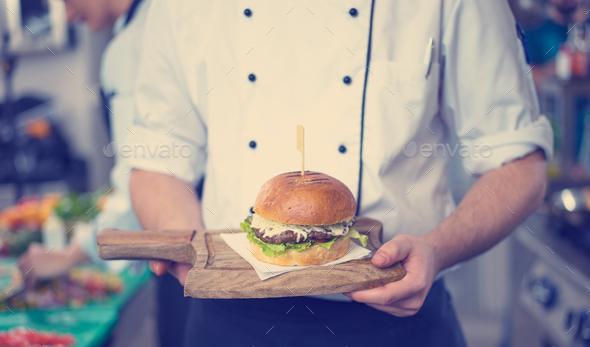 chef finishing burger - Stock Photo - Images