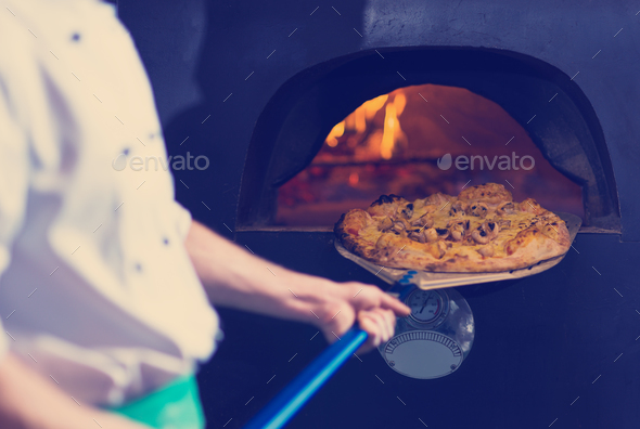 chef removing hot pizza from stove - Stock Photo - Images