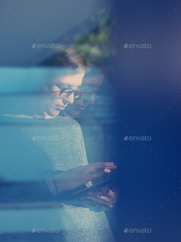 Woman using tablet at home by the window - Stock Photo - Images