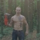 Portrait of Brutal Man Stand with Chainsaw in Hand in the Forest - VideoHive Item for Sale