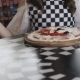 Smiling Girl Spinning the Pizza and Smiling at Camera in Cafe - VideoHive Item for Sale