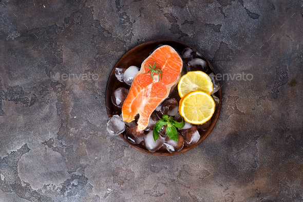 Salmon steaks on ice withlemon slice on wooden plate - Stock Photo - Images